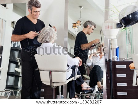 Male hairdresser styling senior woman's hair at beauty salon