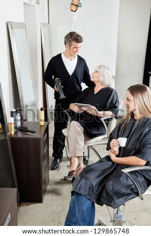 Male hairdresser with female client's in beauty salon - stock photo