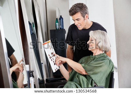 Male hairdresser with senior female client selecting color from catalogue at hair salon - stock photo