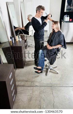 Male hairstylist cutting customer's hair with senior client waiting in background - stock photo