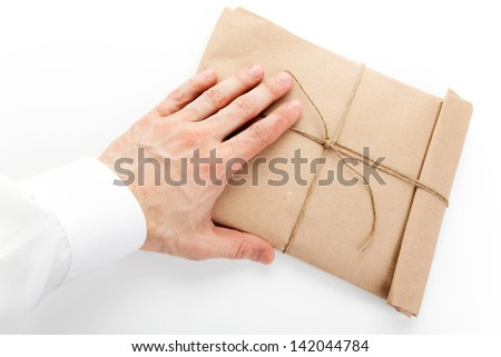 Male hand and envelope tied with a rope on white background - stock photo
