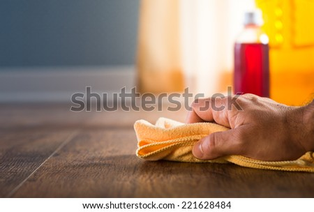 Male hand applying wood care products and cleaners on hardwood floor surface. - stock photo