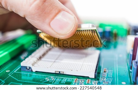 male hand assembles computer parts on the board
