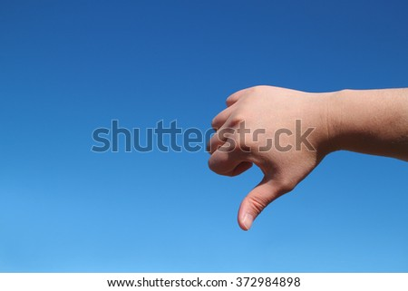 male hand bad gesture in the blue sky - stock photo