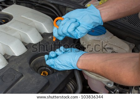 Male hand checking the oil level in the engine bay of vehicle - stock photo
