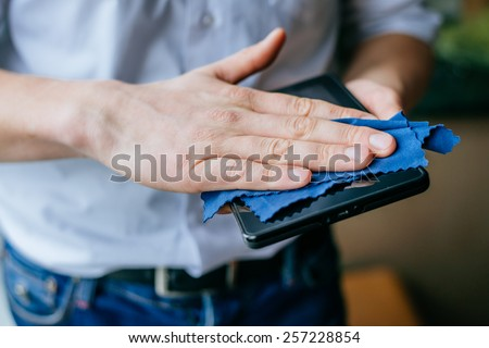 male hand cleaning tablet screen with cloth - stock photo