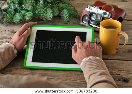 Male hand clicks blank screen tablet computer on the wooden table closeup. Next on the table vintage camera and a large cup of coffee. Copy space. Top view. Free space for text - stock photo