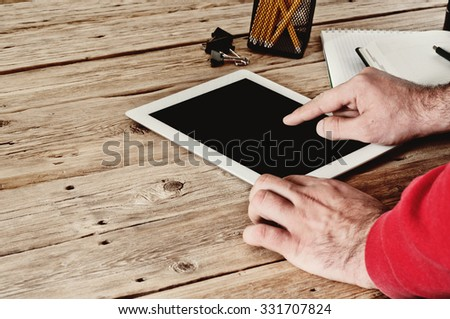 Male hand clicks on a blank screen tablet computer closeup. The concept of working with a tablet computer. Copy space. Free space for text. Top view. Toned photo of a vintage style - stock photo