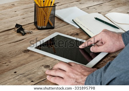 Male hand clicks on a blank screen tablet computer closeup. The concept of working with a tablet computer. Top view. Copy space. Free space for text - stock photo