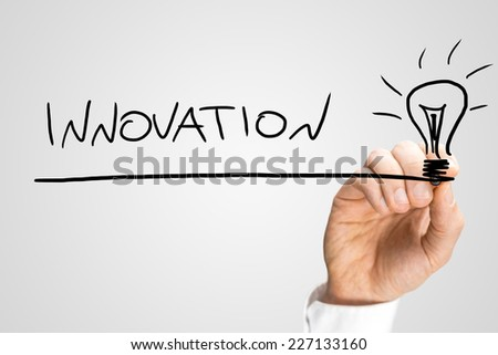 Male hand drawing light bulb and writing word Innovation on a virtual screen with black marker. Over grey background. - stock photo