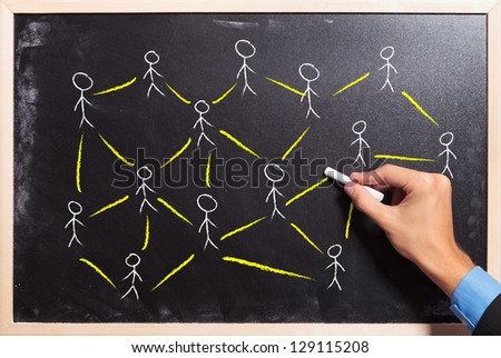 male hand drawing on a blackboard: social networking or teamwork concept - stock photo