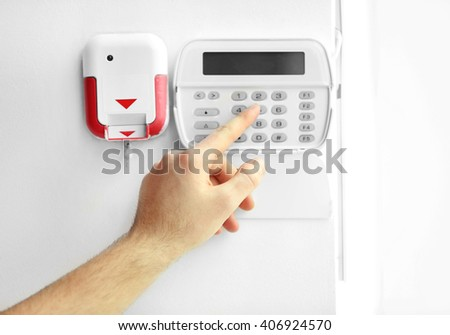 Male hand entering code on security system keypad indoors - stock photo
