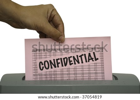Male hand, feeding a pink piece of paper with the word confidential and random numbers into a shredder. Saved including clipping path.