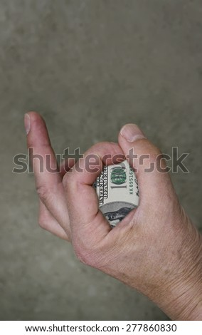 Male hand gesturing OK sign with a hundred dollar banknote, vertical studio shot - stock photo