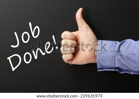 Male hand gives a thumbs up gesture for the phrase Job Done on a blackboard