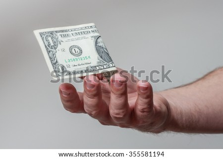 Male hand giving American one dollar bill