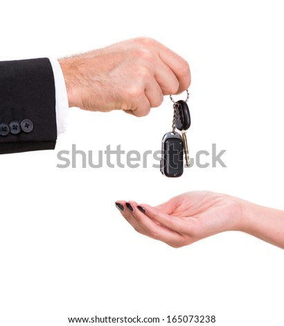Male hand giving car key to female hand on a white background