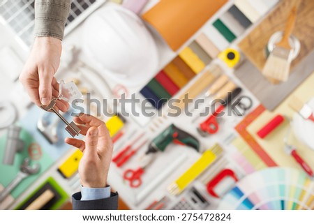 Male hand handing a key to a house owner, home construction and renovation tools on background, top view - stock photo