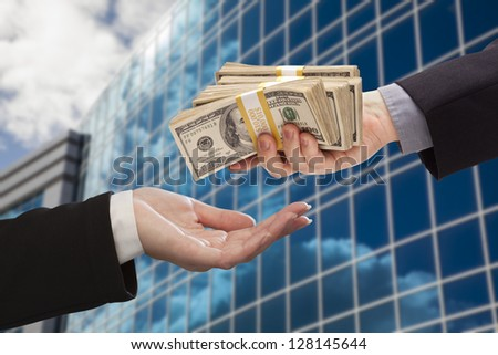Male Hand Handing Stack of Cash to Woman with Corporate Building. - stock photo