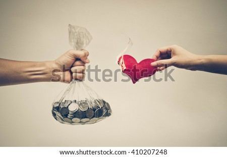 Male hand holding a bag full of coins trying to buy a burnt red hearts from female hand  - stock photo