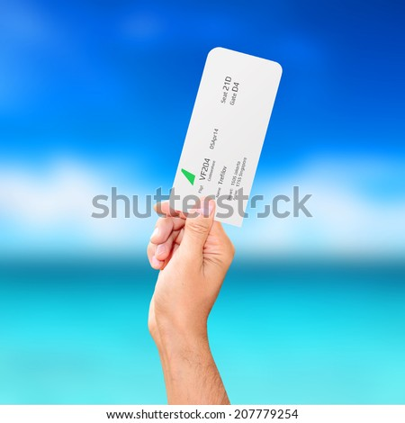 male hand holding a boarding pass - stock photo