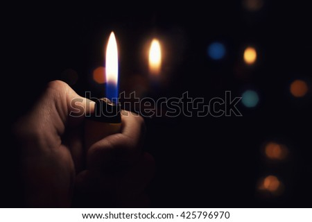 Male hand holding a burning lighter in the dark - stock photo