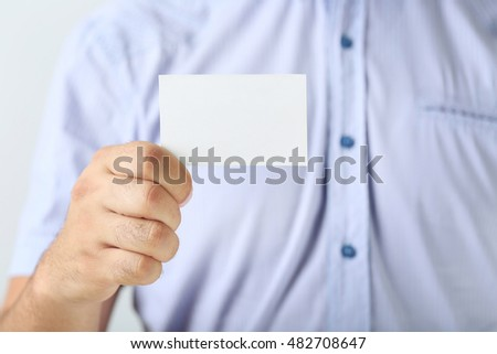 Male hand holding a business card