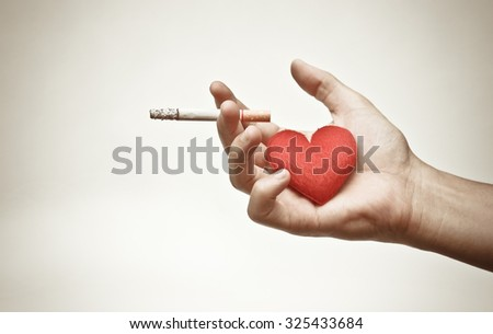 male hand holding a cigarette with a red heart / making to right decision about smoking concept - stock photo