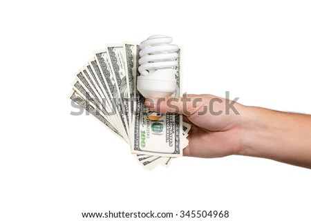 Male hand holding a fan of hundred-dollar bills, and energy-saving light bulb - stock photo