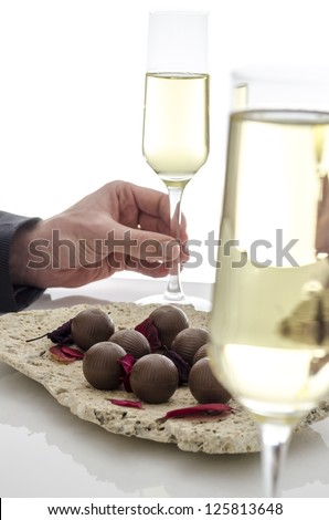 Male hand holding a glass of wine on a white table. - stock photo