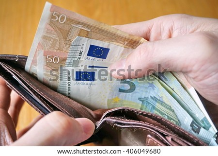 Male hand holding a leather wallet and withdrawing European currency (Euro, EUR) - stock photo