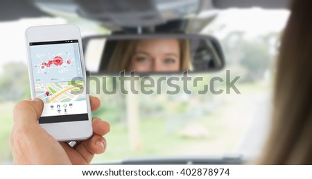 Male hand holding a smartphone against young woman in the drivers seat looking in the mirror - stock photo