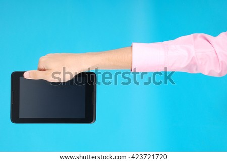 Male hand holding a touchscreen isolated on blue background - stock photo