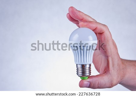 Male hand holding a white led light bulb - stock photo