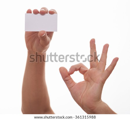 """Male hand holding an empty business card and showing """"OK"""" sign, white background - stock photo"""