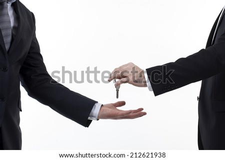 Male hand holding apartment keys and handing it over to another person isolated