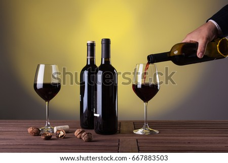 Male hand holding bottle of red wine and pouring into a wineglass
