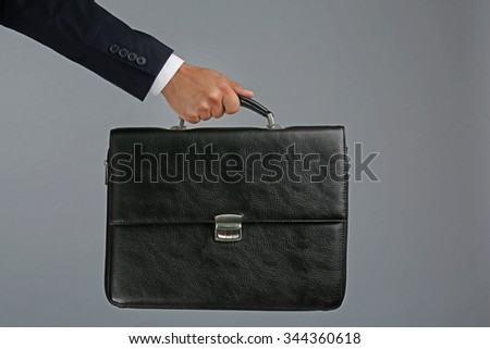 Male hand holding briefcase on gray background
