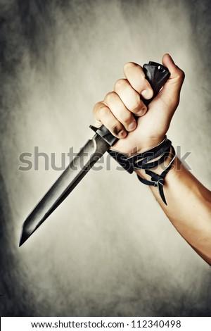 male hand holding combat black Knife - stock photo