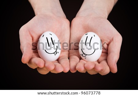 male hand holding eggs with smiley faces