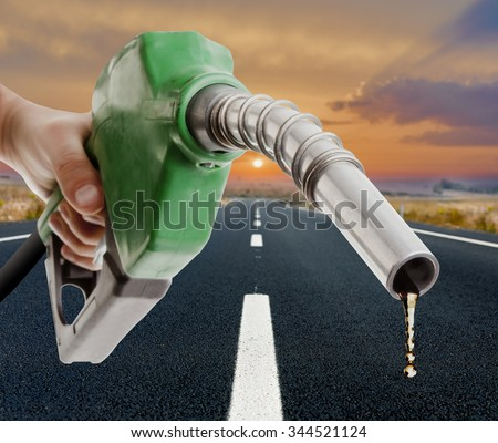 Male hand holding gas pump with one last drop and the road on the background - stock photo