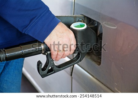 male hand holding gasoline pump into the tank of a car - stock photo