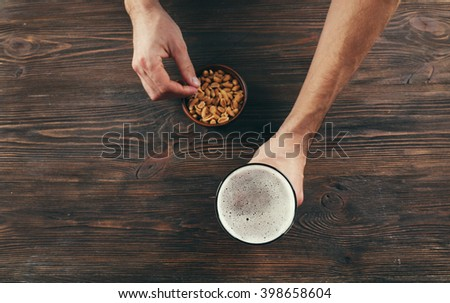 Male hand holding glass of beer on wooden background - stock photo