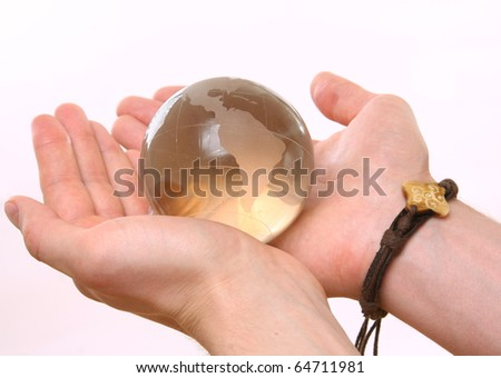 Male hand holding glass sphere in hand - stock photo