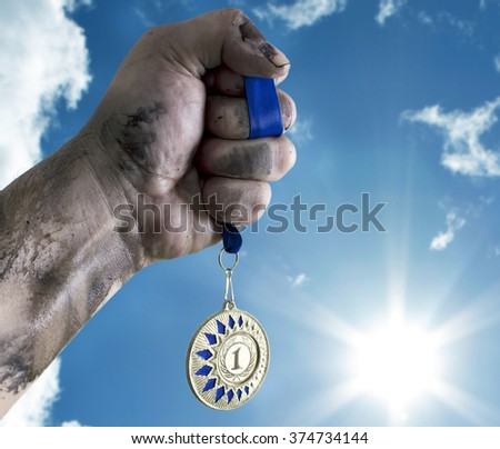 Male hand holding gold medal against the sky. - stock photo