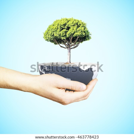 Male hand holding half a globe with large tree on blue background. Green earth concept. Elements of this image furnished by NASA. 3D Rendering