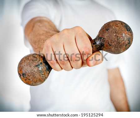 Male hand holding old rusty dumbbell - stock photo