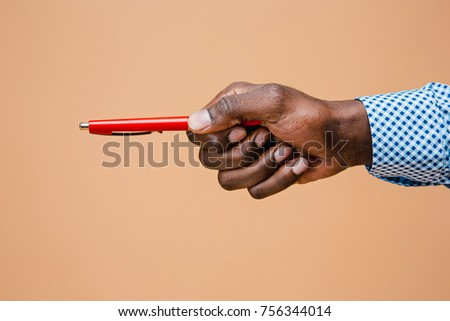 Male hand holding pencil, isolated on studio brown background