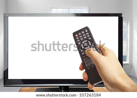 Male hand holding remote control and the TV in a modern room - stock photo