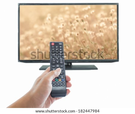 Male hand holding remote control to the TV - stock photo